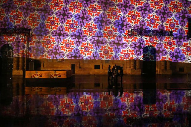 3D projections designed by students of the Malta College of Arts, Science and Technology are shown on the facade of the Presidential Palace and reflected in the rain-soaked ground during a rehearsal for New Year's Eve celebrations in Valletta. (Photo by Darrin Zammit Lupi/Reuters)