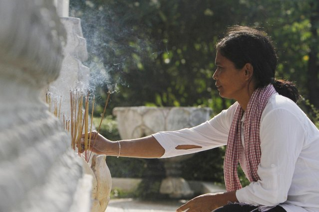 A Cambodian woman burns incense sticks as she prays in front of a stupa containing hundreds of human skulls and bones of victims in Khmer Rouge regime, at Choeung Ek memorial on the outskirts of Phnom Penh, Cambodia, Friday, April 17, 2015. (Photo by Heng Sinith/AP Photo)