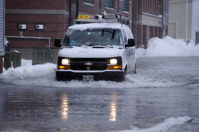 An electric utilities truck drives over a flooded road along the waterfront during a snowstorm, Thursday, January 2, 2014, in Portland, Maine. Astronomical high tides, strong winds and frigid temperatures are all factors in this latest storm to hit the Northeast. (Photo by Robert F. Bukaty/AP Photo)