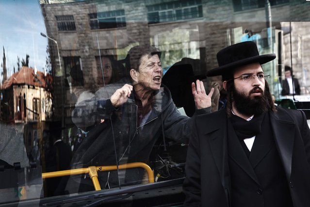A woman on a bus reacts as Ultra-Orthodox Jews block a bus during a protest against Ultra-Orthodox Jewish youth who serve in the Israeli army, in the neighbourhood of Mea Shearim in Jerusalem, on January 17, 2017. (Photo by Menahem Kahana/AFP Photo)