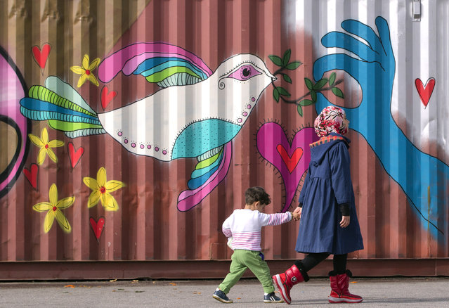 Children walk by a painted container as people wait in line for food handouts outside an overcrowded shelter area for migrants at the Athens' port of Piraeus, Tuesday, March 1, 2016. (Photo by Vadim Ghirda/AP Photo)