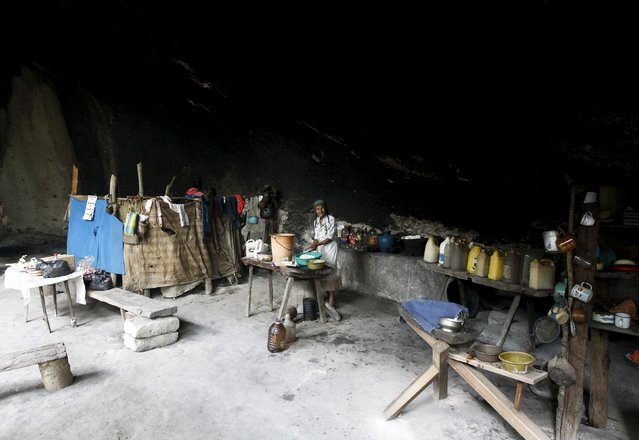 Francisca Gomez washes dishes inside her home, a cave where she has been living for the past 50 years, in the mountains on the outskirts of Chusmuy April 21, 2015. (Photo by Jorge Cabrera/Reuters)