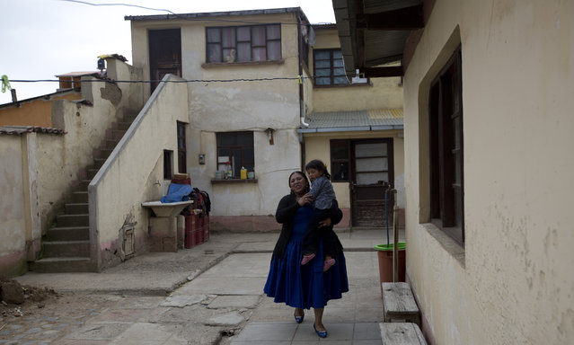 Reyna Torrez, a veteran cholita wrestler who uses the ring name Leydi Huanca, carries her daughter Lydia after an interview at her home in El Alto, Bolivia, Monday, February 18, 2019. Torrez, 29, is teaching a new generation of female wrestlers as her generation of fighters gradually dwindled to just seven. (Photo by Juan Karita/AP Photo)