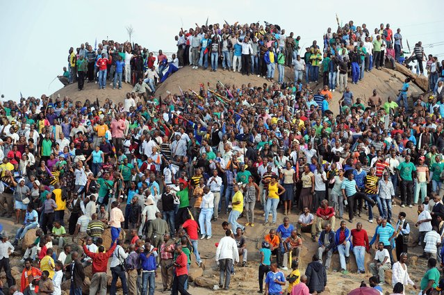 People gather on a hill in Marikana on August 23, 2012 after attending a memorial service for the 44 people killed in a wildcat strike at Lonmin's Marikana mine. (Photo by AFP Photo/STR)