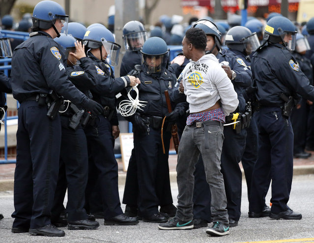 Police detain a man after a march to City Hall for Freddie Gray, Saturday, April 25, 2015 in Baltimore. (Photo by Alex Brandon/AP Photo)