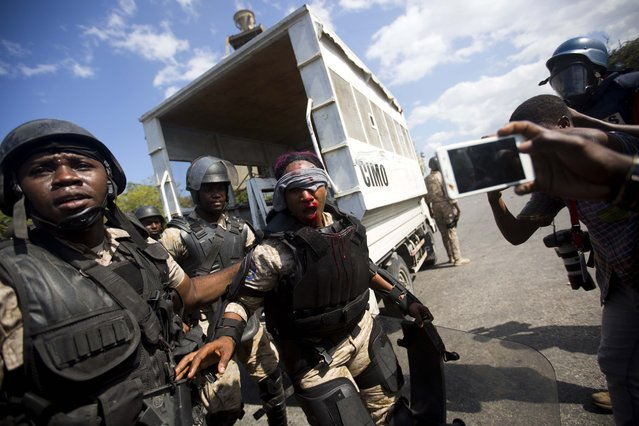 A national police officer is helped by fellow officers after she was hit in the face with a rock thrown by protesters demanding the resignation of Haitian President Jovenel Moise near the presidential palace in Port-au-Prince, Haiti, Wednesday, February 13, 2019. (Photo by Dieu Nalio Chery/AP Photo)