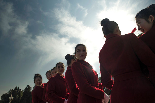 Hostesses pose for photographers during the 2nd plenary session of the National People's Congress outside the Great Hall of the People in Beijing on March 9, 2016. China's Communist-controlled parliament opened its annual session on March 5 and is expected to appove a new five-year plan to tackle slowing growth in the world's second-largest economy. (Photo by Fred Dufour/AFP Photo)