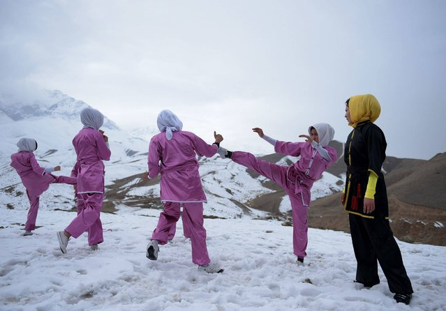 In this photograph taken on January 29, 2017, Afghan members of a Wushu martial arts group display their skills as they pose for a photograph at the Shahrak Haji Nabi hilltop overlooking Kabul. Afghanistan's first female Wushu trainer, Sima Azimi, 20, is training 20 Afghan girls aged between 14-20 at a Wushu club in Kabul, after learning the sport while living as a refugee in Iran. (Photo by Wakil Kohsar/AFP Photo)