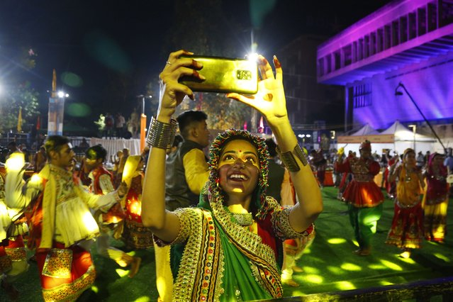 An Indian girl wearing traditional attire takes selfie as others perform the Garba, a dance of Gujarat state, to celebrate the Hindu festival Navratri in Ahmedabad, India, Thursday, October 7, 2021. Navratri, or nine nights festival, began Thursday. (Photo by Ajit Solanki/AP Photo)