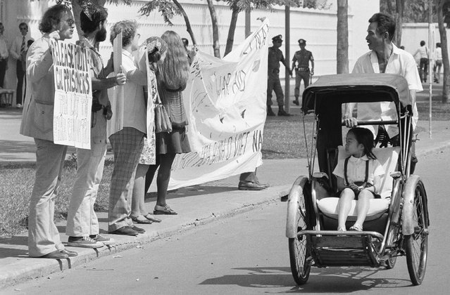 A little girl in a pedicab, and her driver stare as they pass a demonstration of nine anti-war activists before the United States embassy in Saigon, Friday, Jan. 25, 1975. The activists, led by David Harris, left, of Menlo Park, Calif. former husband of folk singer Joan Baez, passed out leaflets demanding the end of U.S. intervention in South Vietnam. (Photo by AP Photo)