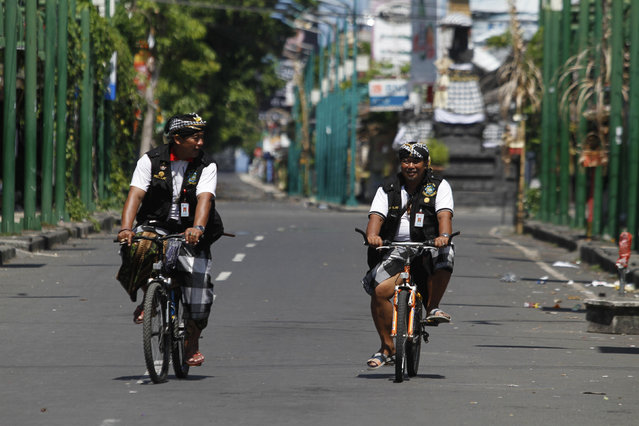 Pecalang, or traditional village security, ride bikes while on an inspection during Nyepi in Kuta, on Indonesian resort island of Bali, March 9, 2016. Nyepi is a day of silence to celebrate the Balinese New Year, reserved for self-reflection, where people are not allowed to use lights, light fires, work, travel or enjoy entertainment. (Photo by Roni Bintang/Reuters)