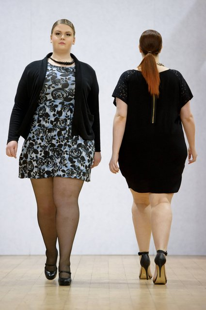 Models wear a design created by Plus Size Fashion during London Fashion Week Autumn/Winter 2014, at Vinopolis in central London, Friday, February 14, 2014. (Photo by Jonathan Short/AP Photo)