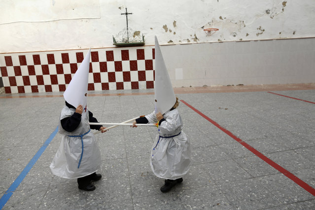 Children wearing hoods as penitents play after taking part in a procession at a school on the eve of Holy Week in the Andalusian capital of Seville, southern Spain March 18, 2016. (Photo by Marcelo del Pozo/Reuters)