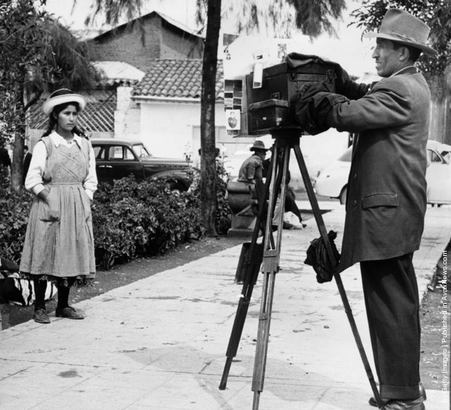 A street photographer preparing to take a picture of a Peruvian girl, 1950