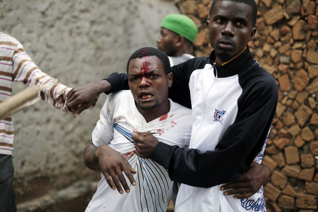 Jean Claude Niyonzima, a suspected member of the ruling party's Imbonerakure youth militia, is restrained as a mob gathers around his house, as protests continue against  President Pierre Nkurunziza's decision to seek a third term in office in the Cibitoke district of Bujumbura, Burundi, Thursday May 7, 2015. (Photo by Jerome Delay/AP Photo)