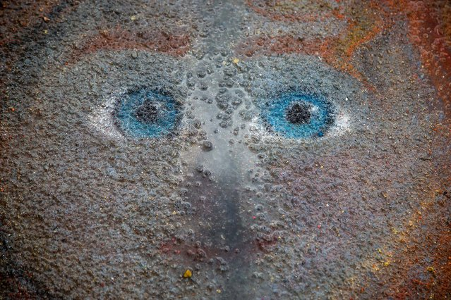 An afternoon rain shower begins to wash away the chalk face of a painting. (Photo by Greg Lovett/The Palm Beach Post)