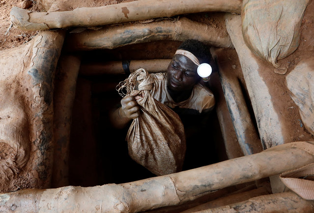 An artisanal miner climbs out of a gold mine with a bag of rocks broken off from inside the mining pit at the unlicensed mining site of Nsuaem Top in Ghana, November 24, 2018. (Photo by Zohra Bensemra/Reuters)