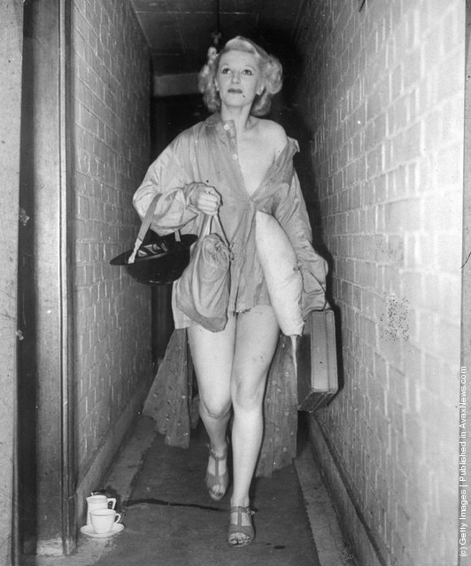 Sonia Stacpoole, a scantily-clad member of the Windmill cast makes her way along a narrow corridor to the theatre air raid shelter clutching a tin-hat and a pillow
