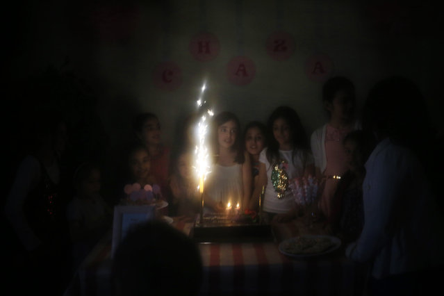 This Saturday, April 25, 2015 image shows girls celebrating a birthday at a home in Beirut, Lebanon. This photo was shot through the lowered veil of a niqab, which is worn by some conservative Muslim women. (Photo by Hassan Ammar/AP Photo)