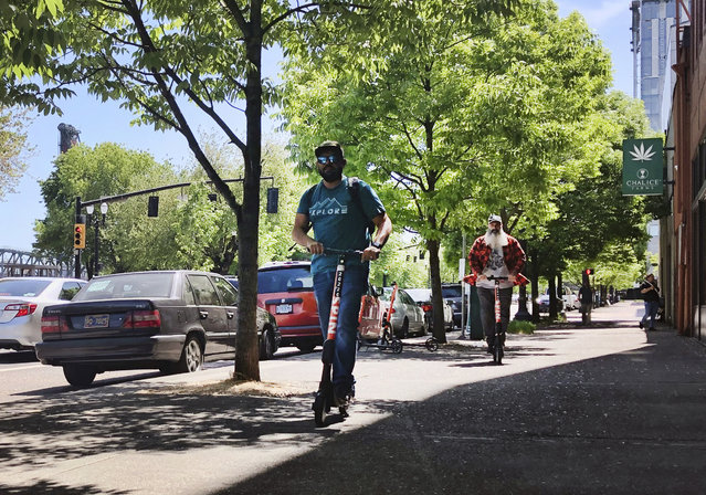 Motorists ride on electric scooters along a street in downtown Portland, Ore., Thursday, May 9, 2019. A disability rights nonprofit group in Oregon filed a letter of complaint Thursday with the city of Portland over new rules about an electric scooter pilot program. (Photo by Gillian Flaccus/AP Photo)