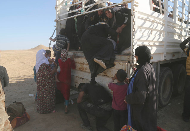 A member of elite counter terrorism forces helps women and children fleeing their homes during clashes between Iraqi security forces and Islamic State group in Hit, 85 miles (140 kilometers) west of Baghdad, Iraq, Monday, April 4, 2016. Families, many with small children and elderly relatives say they walked for hours Monday through desert littered with roadside bombs to escape airstrikes and clashes. (Photo by Khalid Mohammed/AP Photo)