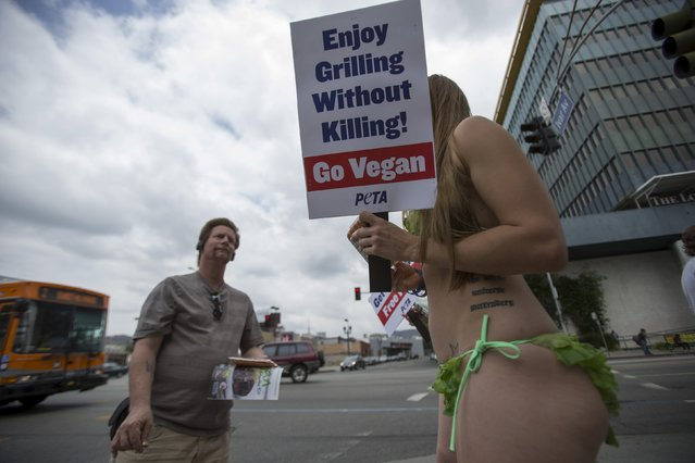 An activist from People for the Ethical Treatment of Animals (PETA) holds a sign promoting a vegan diet in Los Angeles, California May 21, 2015. (Photo by Mario Anzuoni/Reuters)