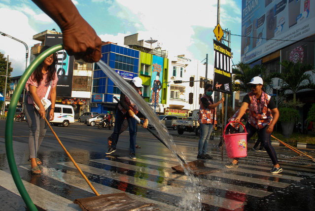 Women clean a zebra crossing in preparation for Eid al-Fitr celebrations in Surakarta, Indonesia on May 30, 2019. (Photo by Riau Images/Barcroft Media)