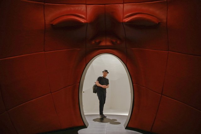 """A visitor admires the installation """"Intro"""" by architect Fabio Novembre, part of the """"Fuori Salone"""" exhibitions during the Design Week, in Milan, Italy, Thursday, April 14, 2016. (Photo by Luca Bruno/AP Photo)"""