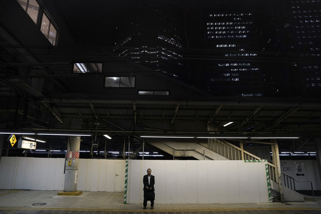 In this Tuesday, May 21, 2019, photo, a man in a black suit waits for a train to arrive on a platform at Shinagawa Station in Tokyo. Operated by the East Japan Railway Co., the Yamanote Line in Tokyo makes a loop around the center of the city, connecting 29 stations that include key stops such as Shinjuku, Shibuya and Ikebukuro. A complete loop of about an hour offers scenes of Japanese daily lives. (Photo by Jae C. Hong/AP Photo)