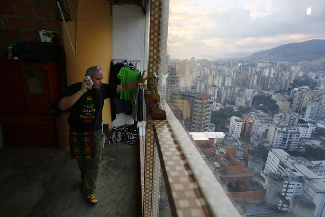 """Nicolas Alvarez speaks on the telephone in his apartment on the 27th floor of the """"Tower of David"""" skyscraper in Caracas February 5, 2014. (Photo by Jorge Silva/Reuters)"""