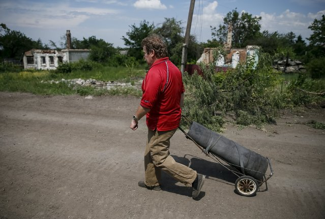 """A local resident walks along the street in the town of Maryinka, eastern Ukraine, June 5, 2015. Ukraine's president told his military on Thursday to prepare for a possible """"full-scale invasion"""" by Russia all along their joint border, a day after the worst fighting with Russian-backed separatists in months.  REUTERS/Gleb Garanich"""