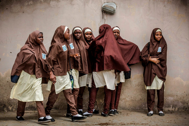 """A group of girls leave their school during a rally by All Progressives Congress (APC) party supporters celebrating the re-election of the incumbent president and the leader of APC, in Kano on February 27, 2019. Nigeria's President Muhammadu Buhari said his re-election was """"free and fair"""", after his beaten rival denounced the results as a """"sham"""" and promised a legal challenge that could dominate politics for weeks. The 76-year-old one-time military ruler's victory was confirmed late on February 26, 2019, after rescheduled polling blamed on logistical difficulties. (Photo by Luis Tato/AFP Photo)"""