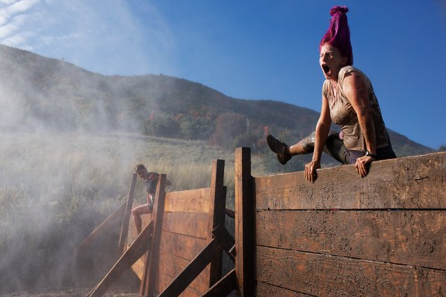 """The Dirty Dash is a new kind of race, a mud run obstacle course where """"a military boot camp meets your inner five-year-old's fantasy"""". One of the first tricky hurdles to overcome is a series of super slick six-foot walls. (Photo by Sol Neelman)"""