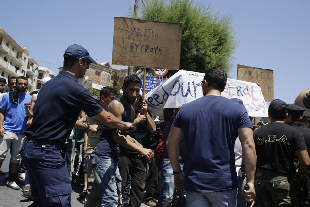 Police and coast guard scuffle with Syrians during a protest by refugees and migrants, demanding better living conditions and faster processing of their asylum registrations at the port of Mytilene, on the northern Greek island of Lesvos on Wednesday, June 17, 2015. The Aegean island has borne the brunt of a huge influx of migrants from the Middle East, Asia and Africa crossing from Turkey to nearby Greek islands. More than 50,000 migrants have arrived in Greece so far this year. The banner reads ''Documents, registration.'' (AP Photo/Thanassis Stavrakis)