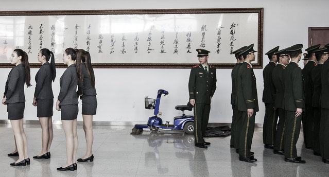 A paramilitary police officer (right) turns around as hostesses line up for roll call ahead of the Beijing International Automotive Exhibition in Beijing, China, on Monday, April 25, 2016. Tesla Motors Inc. and BYD Co. are among manufacturers showing 147 new-energy vehicles at this year's show. (Photo by Qilai Shen/Bloomberg)