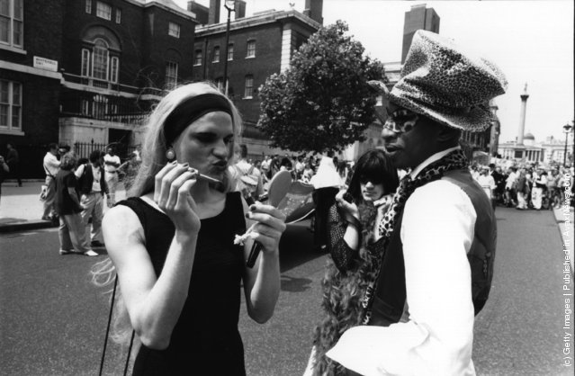 A transvestite adjusts his make-up at the annual Gay Pride march, promoting gay and lesbian rights, London, July 1994