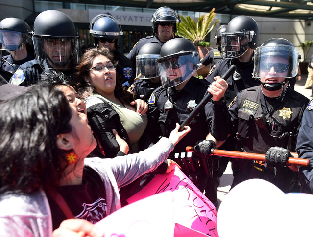 Police in riot gear hold back demonstrators against U.S. Republican presidential candidate Donald Trump outside the Hyatt hotel where Trump is set to speak at the California GOP convention in Burlingame, California, U.S., April 29, 2016. (Photo by Noah Berger/Reuters)