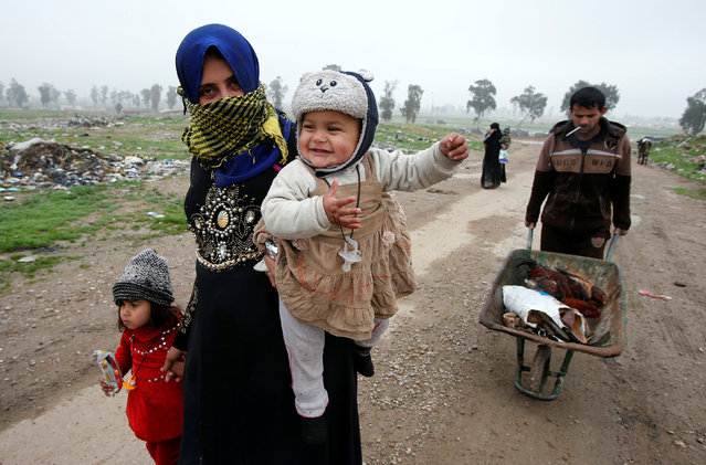 Displaced Iraqi people from different areas in Mosul flee their homes to reach safe areas after clashes broke out as Iraqi forces battle with Islamic State militants in the city of Mosul, Iraq, March 17, 2017. (Photo by Youssef Boudlal/Reuters)