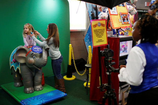 """Karin Albert fixes the hair of her daughter Lily Romanelli, 3, before posing her in an elephant-themed photo booth at Ringling Bros and Barnum & Bailey Circus' """"Circus Extreme"""" show at the Mohegan Sun Arena at Casey Plaza in Wilkes-Barre, Pennsylvania, U.S., April 29, 2016. (Photo by Andrew Kelly/Reuters)"""