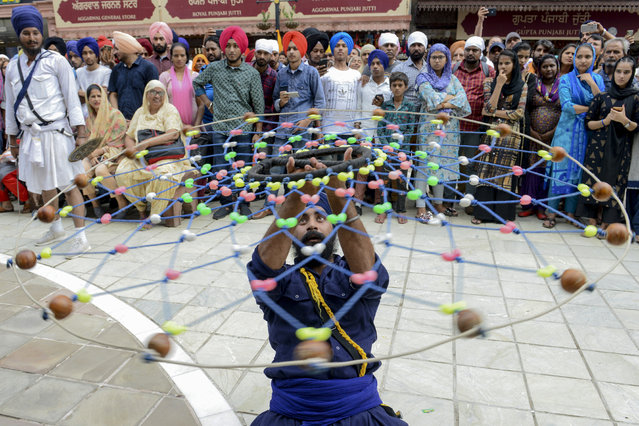 """A Sikh devotee demonstrates his """"Gatka"""" traditional martial art skills during the """"Nagar Kirtan"""" procession to mark the 550th birth anniversary of Guru Nanak Dev, the founder of Sikhism, at the Golden Temple in Amritsar on August 2, 2019. (Photo by Narinder Nanu/AFP Photo)"""