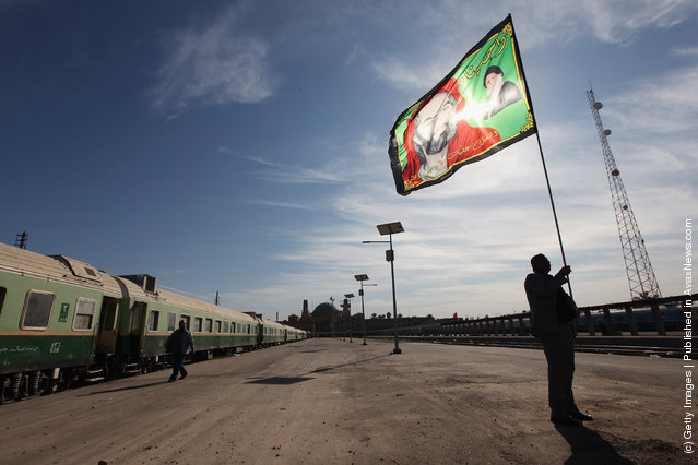 Station master Jawad Khathem prepares to mount a Shi'ite flag on a pole at Baghdad Central Railway Station in preparation for the festival Ashura