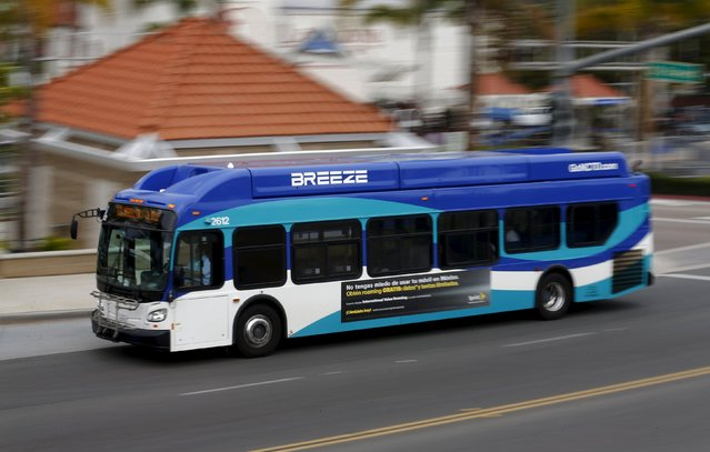 """A natural gas powered North County San Diego transit bus travels through Encinitas, California June 26, 2015. Fifteen years ago, California led the way to cleaner transit buses with strict tailpipe emissions standards that effectively ushered out diesel as the primary fuel for buses in the state and replaced it with natural gas. Now, California is poised once again to take the lead, this time by mandating a switch to so-called """"zero-emission"""" buses by 2040. (Photo by Mike Blake/Reuters)"""