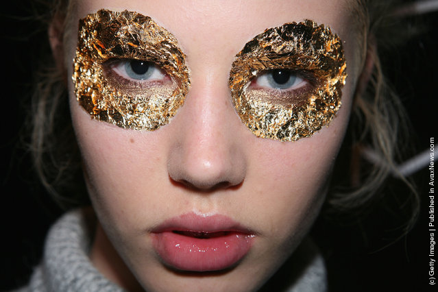 A model has gold leaf eye make-up applied backstage ahead of the Konstantina Mittas catwalk show at the Overseas Passenger Terminal, Circular Quay on day three of Rosemount Australian Fashion Week Spring/Summer 2009/10