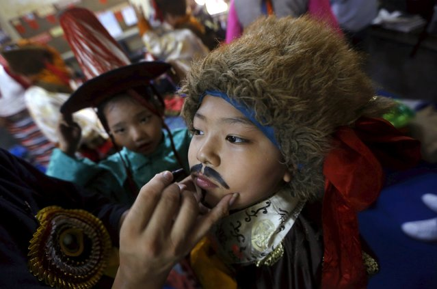 A young Tibetan exile has make-up applied on his face as he gets ready to perform during celebrations marking the 80th birthday of exiled Tibetan spiritual leader Dalai Lama, at Majnu Ka Tila, a Tibetan refugee camp in New Delhi, India, July 6, 2015. (Photo by Adnan Abidi/Reuters)