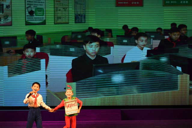 Young children sing and dance in front of images of young Koreans using computers during a concert at the Mangyongdae Children's Palace in Pyongyang, North Korea on May 5, 2016. (Photo by Linda Davidson/The Washington Post)