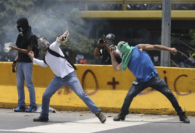 Demonstrators throw stones toward the Venezuelan National Guards during a protest in Caracas, Venezuela, Monday, April 10, 2017. Thousands of people in Venezuela's capital are protesting against the government of President Nicolas Maduro, demanding new elections and vowing to stay in the streets during the usually quiet Easter Week. (Photo by Fernando Llano/AP Photo)
