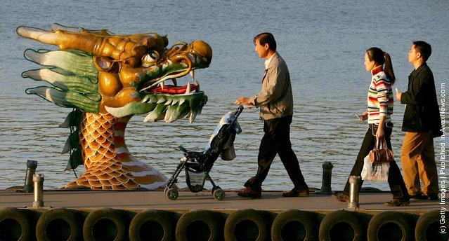 Visitors walk to a tour dragon boat on Kunming Lake at the Summer Palace