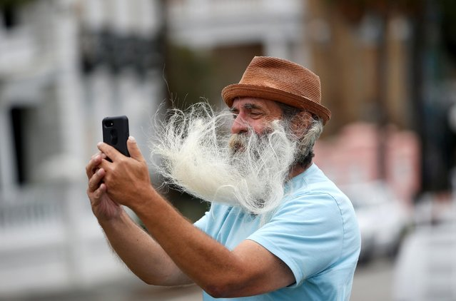 A man's facial hair blows in the wind as he takes a selfie along the waterfront ahead of the arrival of Hurricane Dorian in Charleston, South Carolina, September 4, 2019. The howling west flank of Hurricane Dorian soaked the Carolinas, flooding coastal towns, downing trees and whipping up occasional tornadoes a couple of days after reducing parts of the Bahamas to rubble. (Photo by Randall Hill/Reuters)