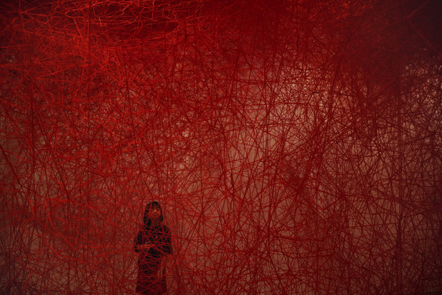 """A woman looks at Chiharu Shiota's art installation titled """"Uncertain Journey"""" at the Mori Art Museum Thursday, September 19, 2019, in Tokyo. (Photo by Jae C. Hong/AP Photo)"""