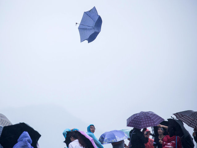 An umbrella blows away as it is caught in strong winds at West Lake in Hangzhou in eastern China's Zhejiang province Saturday, July 11, 2015. (Photo by Chinatopix via AP Photo)